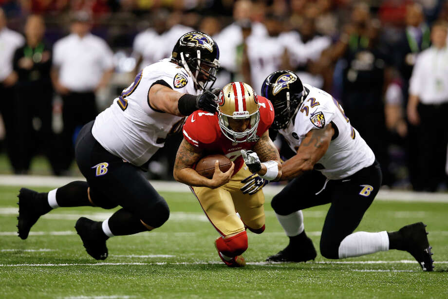 Colin Kaepernick of the San Francisco 49ers is tackled by Haloti Ngata and Ray Lewis of the Baltimore Ravens. Photo: Chris Graythen / 2013 Getty Images