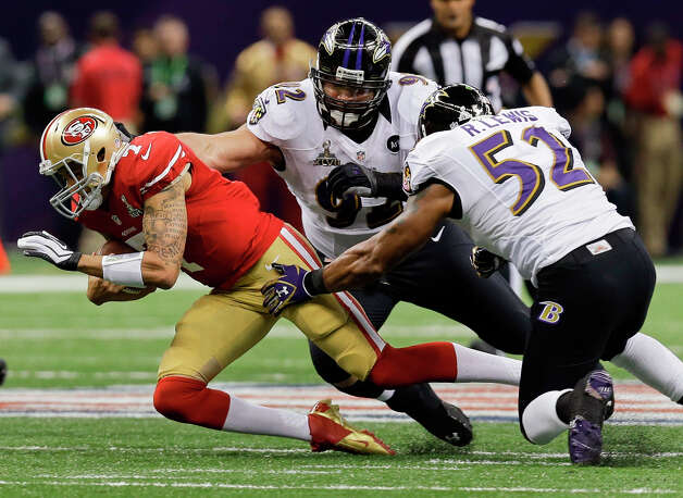 San Francisco 49ers quarterback Colin Kaepernick is tackled by Baltimore Ravens defensive end Haloti Ngata (92) and linebacker Ray Lewis (52) in the first quarter. Photo: Dave Martin