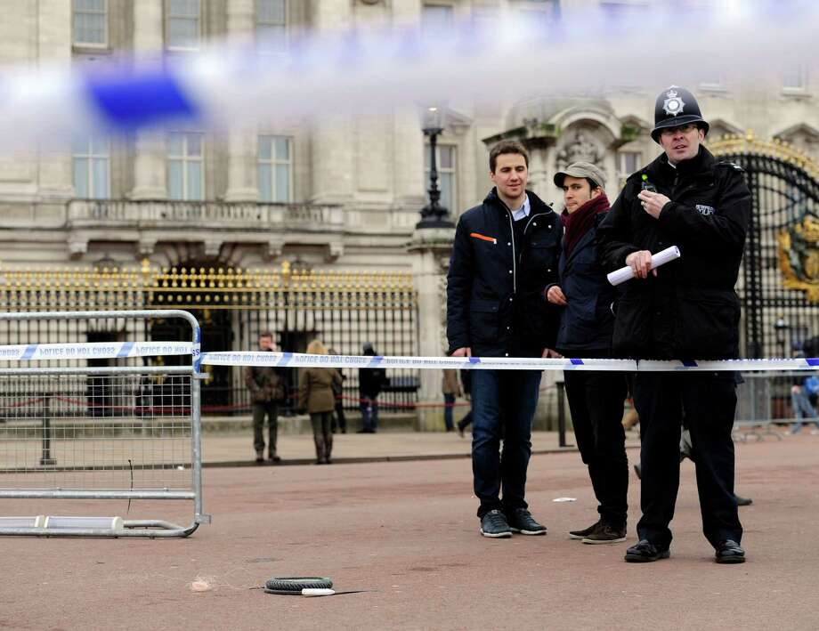 A cornered off area containing knives, a hat and Taser wire outside Buckingham Palace in central London after a man armed with two knives was stunned by police, Sunday Feb. 3, 2013. Scotland Yard said the man, thought to be in his 50s, acted aggressively when challenged by police outside the gates of the heavily touristed landmark on Sunday. Queen Elizabeth II and her husband Prince Philip were at their country retreat, Sandringham Estate, at the time.  (AP Photo/Jonathan Brady/PA)  UNITED KINGDOM OUT - NO SALES - NO ARCHIVES Photo: Jonathan Brady