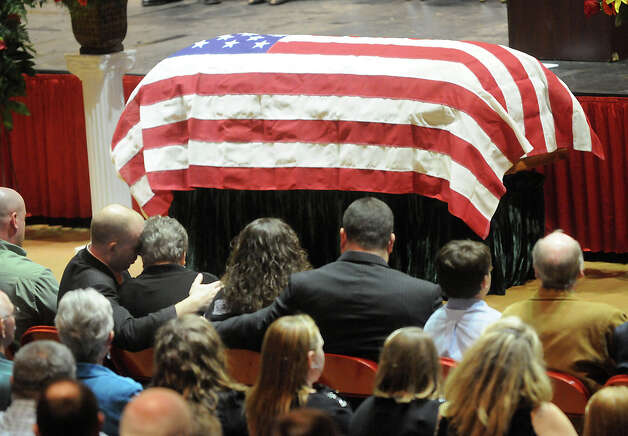 "Family members embrace during the funeral service of Charles ""Chuck"" Poland in Ozark, Ala., Sunday, Feb. 3, 2013. Authorities say Jim Lee Dykes, 65 — a decorated veteran of the Vietnam War known as Jimmy to neighbors — gunned down Poland, a school bus driver, and then abducted a 5-year-old boy from the bus, taking him to an underground bunker on his rural property. (AP Photo/Dothan Eagle, Danny Tindell) Photo: Danny Tindell"