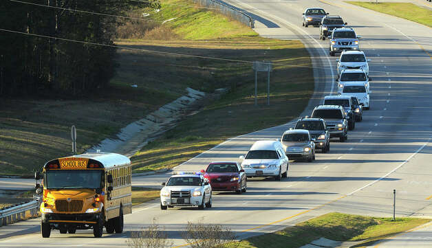 "The funeral procession of slain bus driver Charles ""Chuck"" Poland makes its way down Highway 231 in Ozark, Ala., Sunday Over 60 motorcycles and dozens of school buses join the funeral procession. The Ozark Civic Center was packed with mourners for the funeral. Burial for Poland is in Newton Alabama. (AP Photo/AL.com, Joe Songer) Photo: Joe Songer"