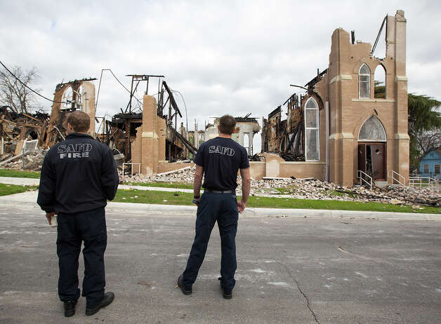 Firefighters David King (left) and Justin Alexander survey the fire damage at what remains of the Childress Memorial Church of God in Christ on the East Side. Photo: Michael Miller, For The Express-News / For the Express-News