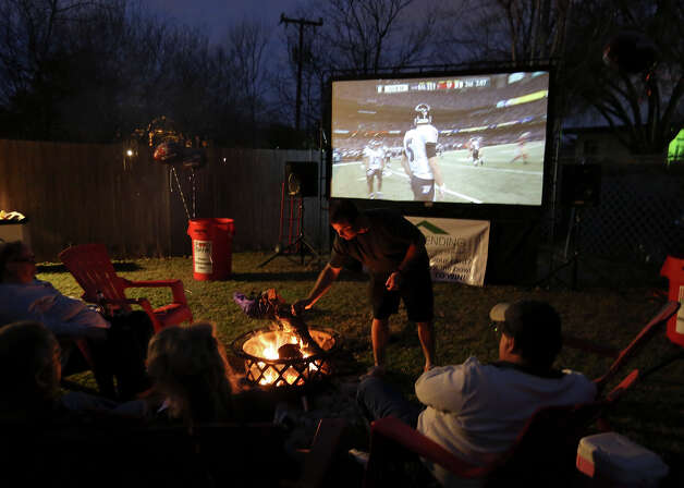 Billy Neel (center) tends to the fire pit during his Super Bowl party Sunday Feb. 3 2013 at his home. Photo: Edward A. Ornelas, San Antonio Express-News / © 2013 San Antonio Express-News