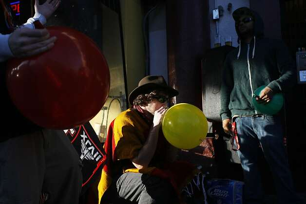 Fans inhale helium from balloons on 16th Street while watching the Super Bowl at Giordano Bros. in the Mission District. Photo: James Tensuan, The Chronicle