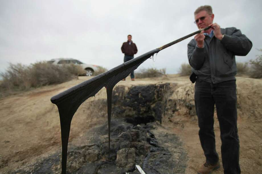 Jeff Prude holds a stick with tar that naturally seeps from the ground dripping from it, in an area known as the McKittrick Brea Pit near Fellows, Calif. Photo: JIM WILSON, STF / NYTNS