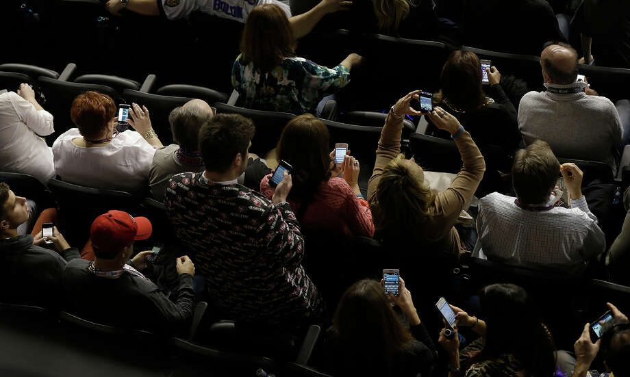 Fans use mobile devices during a power outage at the Superdome in the second half of the NFL Super Bowl XLVII football game between the San Francisco 49ers and the Baltimore Ravens, Sunday, Feb. 3, 2013, in New Orleans. (AP Photo/Gerald Herbert) Photo: Gerald Herbert, ASSOCIATED PRESS / AP2013