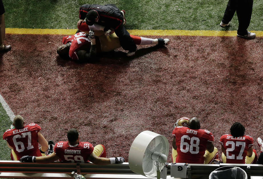 San Francisco 49ers offensive lineman Anthony Davis (76) gets help stretching during a power outage at the Superdome in the second half of the NFL Super Bowl XLVII football game against the Baltimore Ravens, Sunday, Feb. 3, 2013, in New Orleans. Photo: Charlie Riedel, AP / AP
