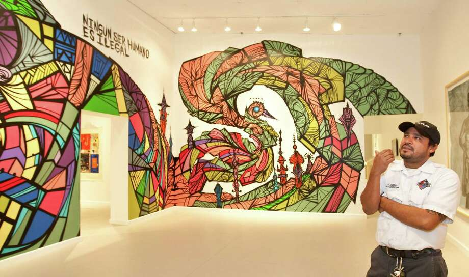 """Houston mural artist Daniel Anguilu contemplates his mural """"Clandestino,"""" which is showing at the Station Museum of Contemporary Art. Photo: Nick De La Torre, Staff / © 2013  Houston Chronicle"""