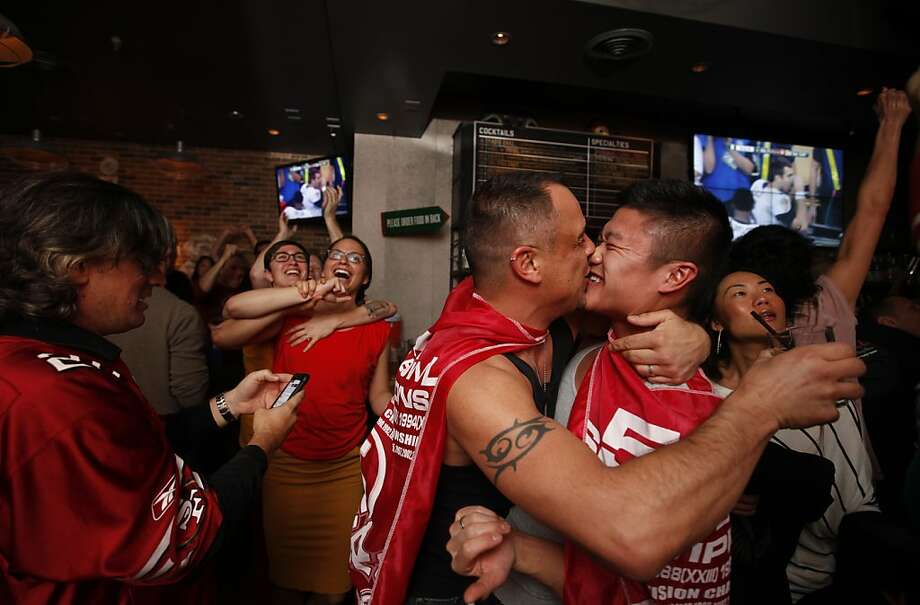 Markus Merlino, left,  kisses his husband Alan as they celebrate the San Francisco 49er scoring in the third quarter against  Baltimore Ravens in the Super Bowl, Sunday Feb. 3, 2013 at the first gay sports bar in  San Francisco, Calif. Photo: Lacy Atkins, The Chronicle