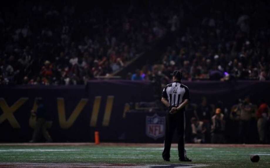 Field judge Craig Wrolstad stands on the field after the lights went out during the second half of NFL Super Bowl XLVII football game Sunday, Feb. 3, 2013, in New Orleans. (AP Photo/Matt Slocum)