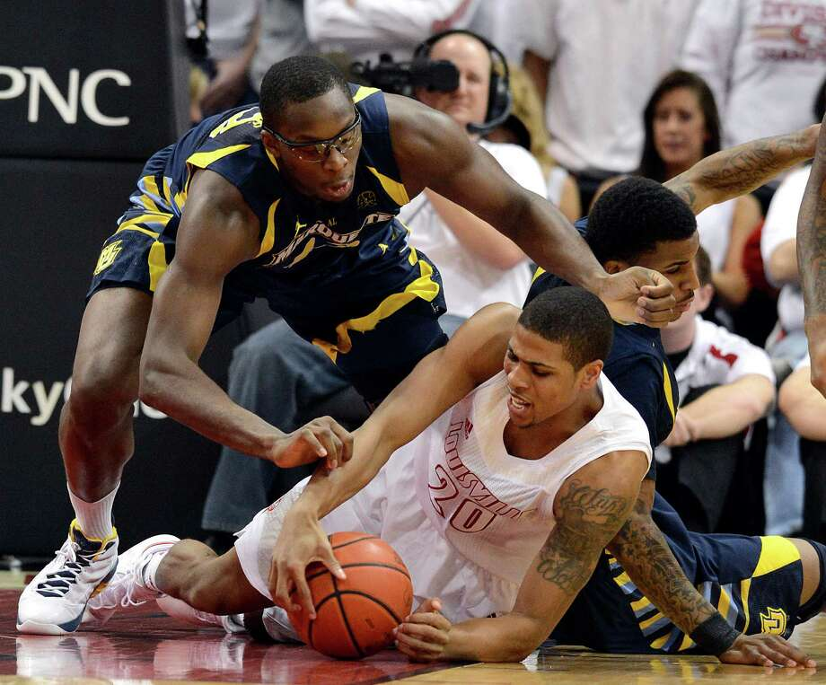 Louisville's Wayne Blackshear, right, battles Marquette's Chris Otule for a loose ball during the first half of their NCAA college basketball game, Sunday, Feb. 3, 2013, in Louisville, Ky. (AP Photo/Timothy D. Easley) Photo: Timothy D. Easley