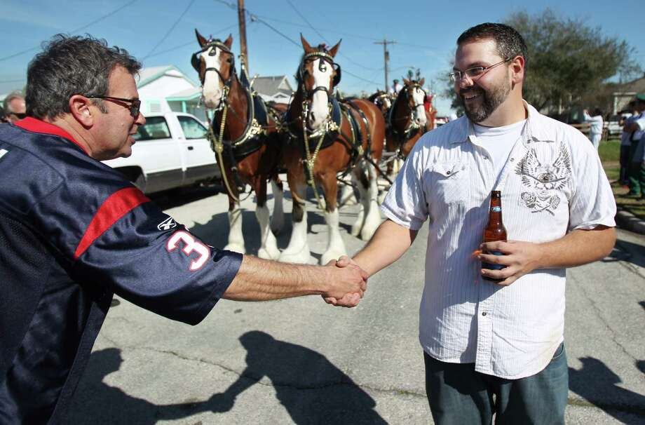 Scott Moga congratulates Ed Drozdik for winning the special visit of the Budweiser Clydesdales to his Super Bowl Party on Sunday, Feb. 3, 2013, in Galveston.  Drozdik was gifted pizza and Budweiser beer for his Super Bowl party. Photo: Mayra Beltran, Houston Chronicle / © 2013 Houston Chronicle