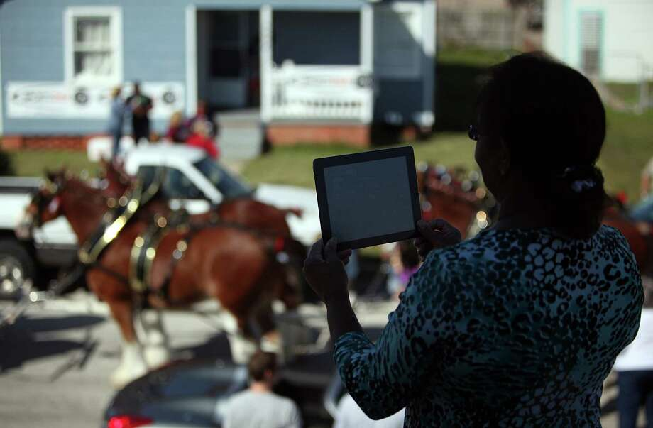 Bea Hilton snaps a photo of Budweiser Clydesdales as they arrive to neighbors Super Bowl Party on Sunday, Feb. 3, 2013, in Galveston. Photo: Mayra Beltran, Houston Chronicle / © 2013 Houston Chronicle