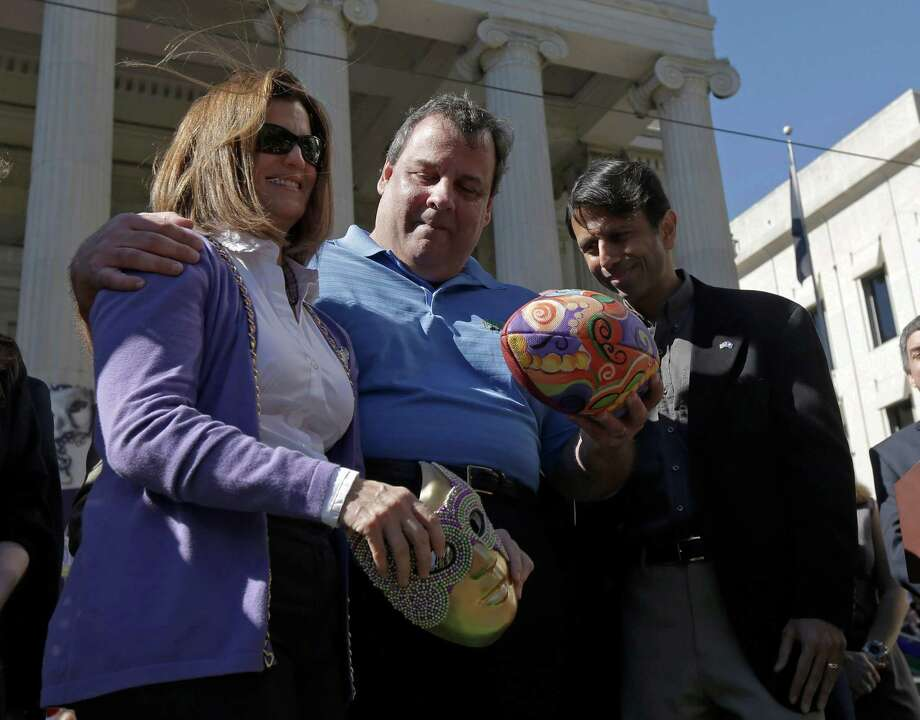 Louisiana Gov. Bobby Jindal, right, presents a ceremonial football to New Jersey Gov. Chris Christie, center, and his wife Patty before the NFL Super Bowl XLVII football game between the San Francisco 49ers and the Baltimore Ravens Sunday, Feb. 3, 2013, in New Orleans. New Jersey will host Super Bowl XLVIII. (AP Photo/Gerald Herbert) Photo: Gerald Herbert
