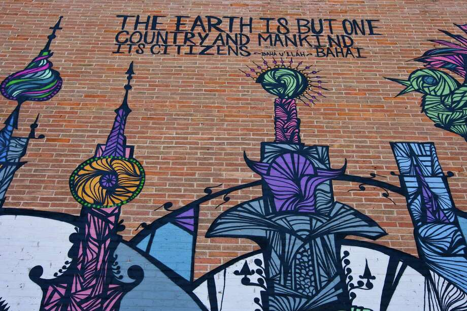 Houston mural artist Daniel Anguilu, says he wrote 'The earth is but one country and mankind it's citizens.' on the Houston Baha'i Center, Wednesday, Jan. 30, in Houston. Anguilu explains that he used symbolism that would represent different religions. Anguilu says he uses house and spray paint for his murals. Photo: Nick De La Torre, Houston Chronicle / © 2013  Houston Chronicle