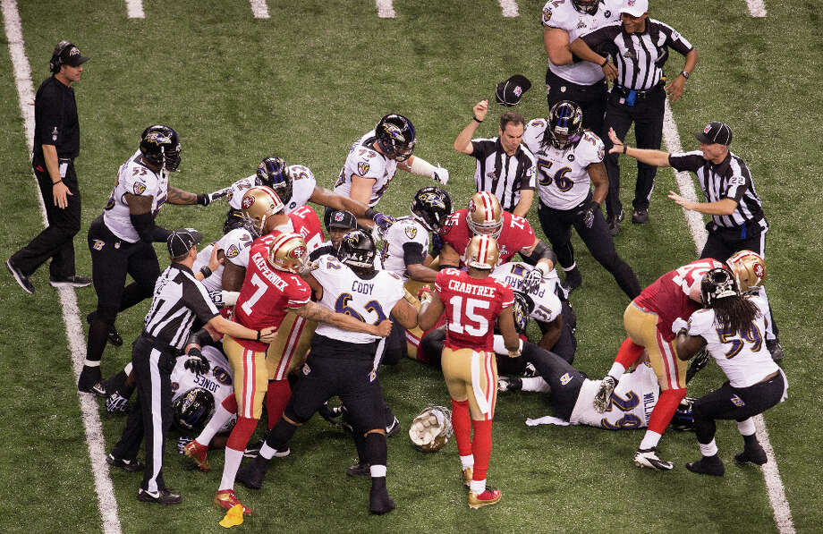 Officials step in to break up a scuffle between San Francisco 49ers and Baltimore Ravens players after the Raven's Ed Reed intercepted a pass during the second quarter. Photo: Smiley N. Pool / © 2013  Houston Chronicle