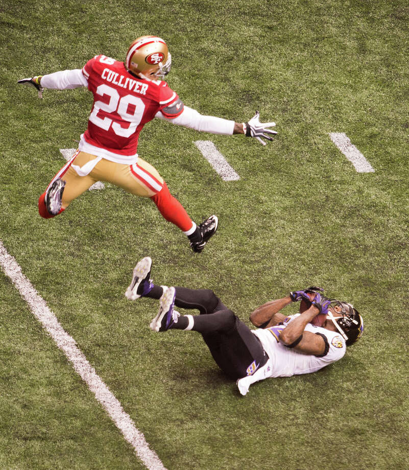 Ravens wide receiver Jacoby Jones (12) falls backwards as he catches a deep pass from Joe Flacco as 49ers defensive back Chris Culliver (29) defends. Photo: Smiley N. Pool, Chronicle / © 2013  Houston Chronicle