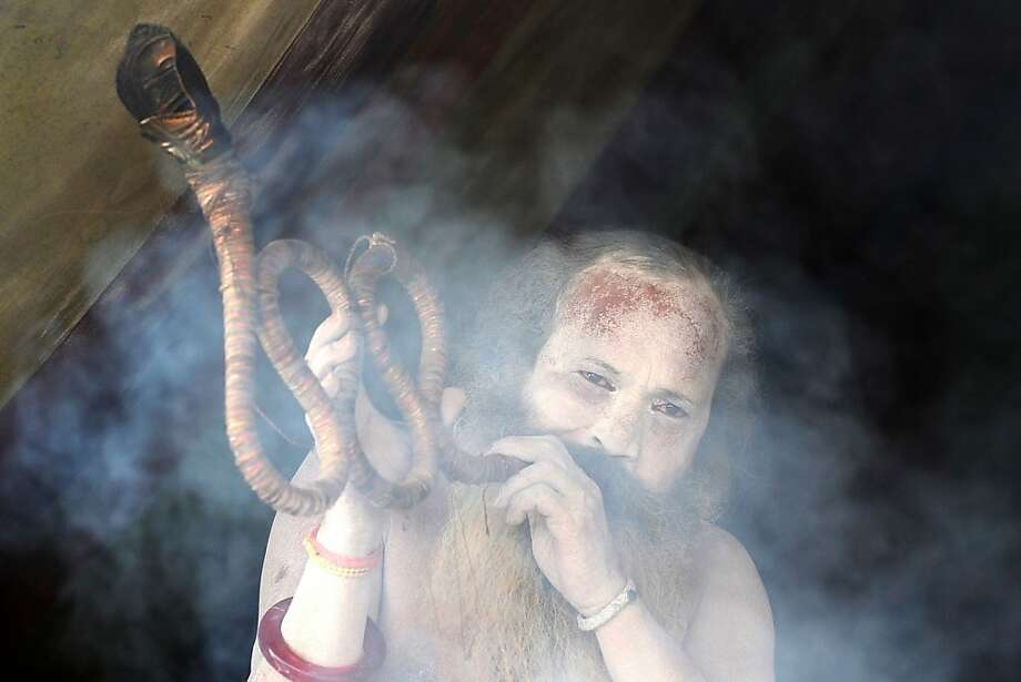An Indian Hindu Sadhu plays a traditional snake-shaped musical instrument at his camp during the Maha Kumbh festival in Allahabad on February 3, 2013.  The Kumbh Mela in the town of Allahabad will see up to 100 million worshippers gather over 55 days to take a ritual bath in the holy waters, believed to cleanse sins and bestow blessings. Photo: Sanjay Kanojia, AFP/Getty Images