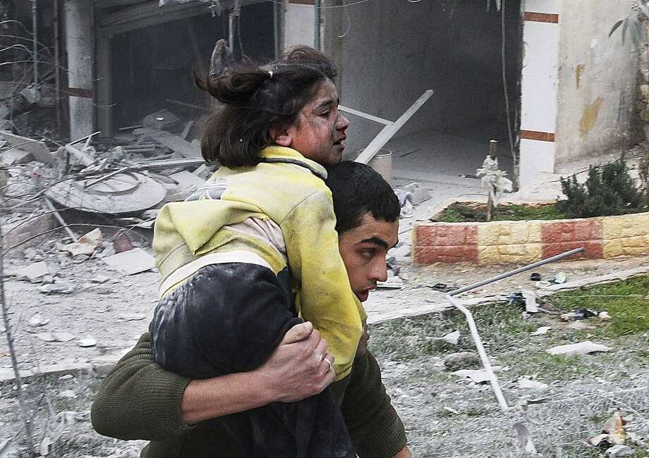 Syrian man carries his sister who was wounded in a government airstrike hit the neighborhood of Ansari, in Aleppo, Syria, Sunday, Feb. 3, 2013.  The Britain-based activist group Syrian Observatory for Human Rights, which opposes the regime, said government troops bombarded a building in Aleppo's rebel-held neighborhood of Eastern Ansari that killed over 10 people, including at least five children. Photo: Abdullah Al-Yassin, Associated Press