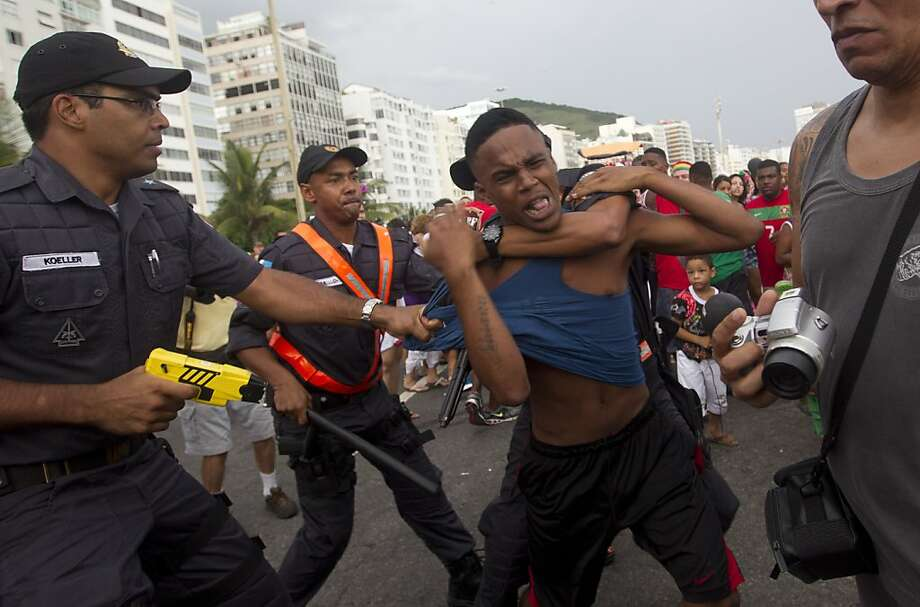 "Brazil's police officers detain an alleged thief during the ""Blocao"" dog carnival parade in Rio de Janeiro, Brazil, Sunday, Feb. 3, 2013. According to Rio's tourism office, Rio's street Carnival this year will consist of 492 block parties, attended by an estimated five million Carnival enthusiasts. Photo: Silvia Izquierdo, Associated Press"