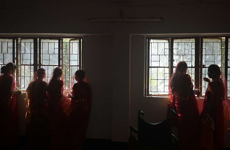 Indian brides stand by a window ahead of a mass marriage ceremony in Haripal, some 70 kms north of K