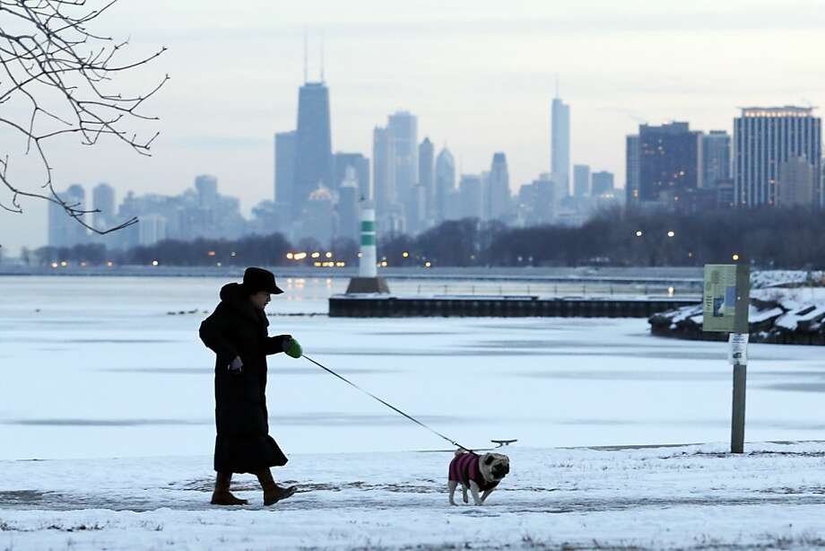 A woman takes a walk with her dog in the snow-covered at Lake Michigan in Chicago, Sunday, Feb. 3, 2013. A fast-moving clipper system is expected to move southeast across the Midwest tonight on a track south of Chicago and is expected to deliver a significant snowfall in the 2 to 5 inch range, with the heaviest amounts across the north portions of the Chicago Metro area, mainly north and east of a line from Rockford to Valparaiso. Photo: Nam Y. Huh, Associated Press