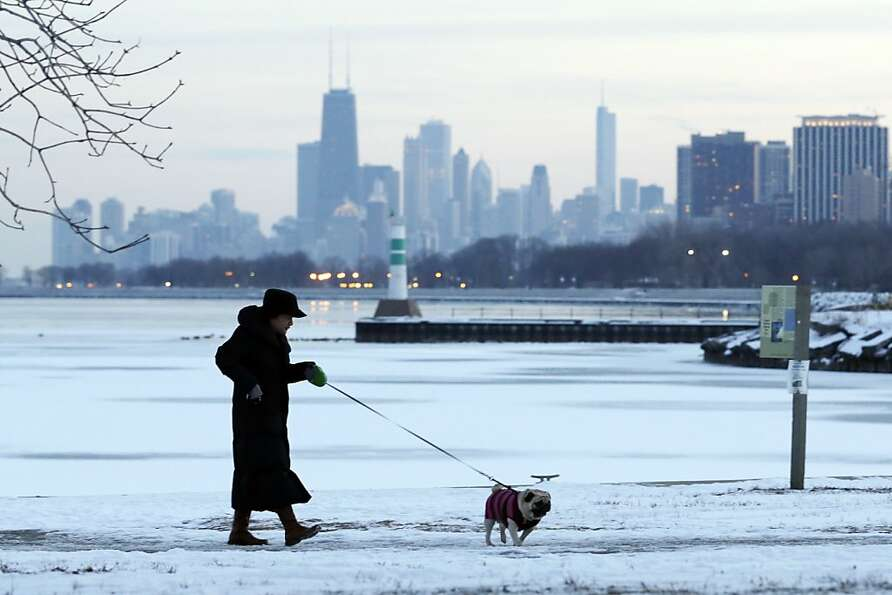 A woman takes a walk with her dog in the snow-covered at Lake Michigan in Chicago, Sunday, Feb. 3, 2