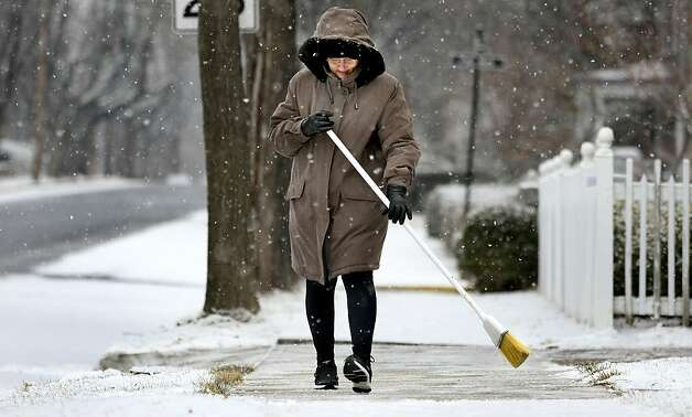 Wanda Gilbert sweeps the sidewalk in front of her Winchester, Va. home as a light snow fell in the area on Sunday morning Feb. 3, 2013. Photo: Ginger Perry, Associated Press