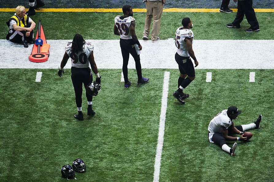 Baltimore Ravens players wait through a delay caused by a power outage during the third quarter of S