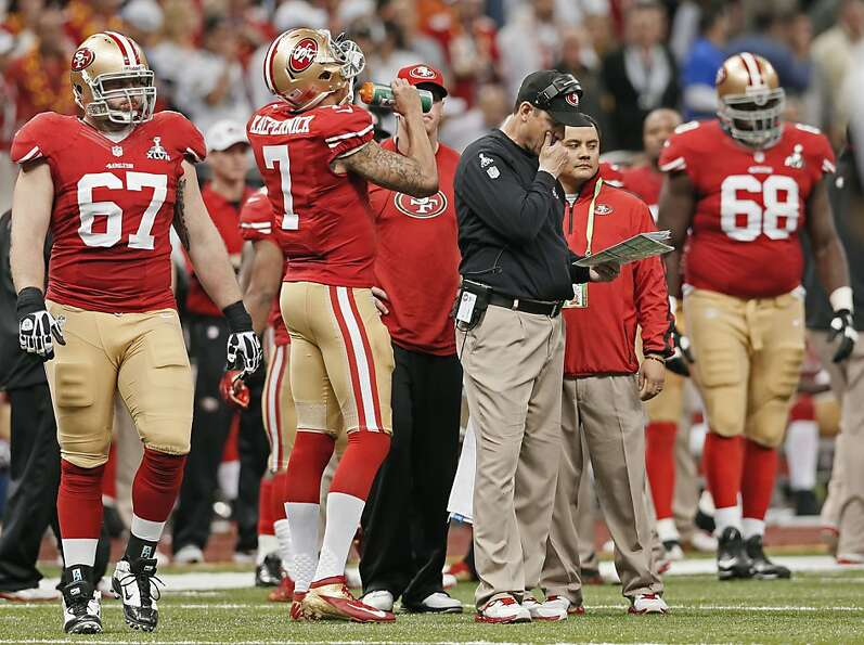 49er head coach Jim Harbaugh looks over his plays late in the fiurth quarter during a time out, as t
