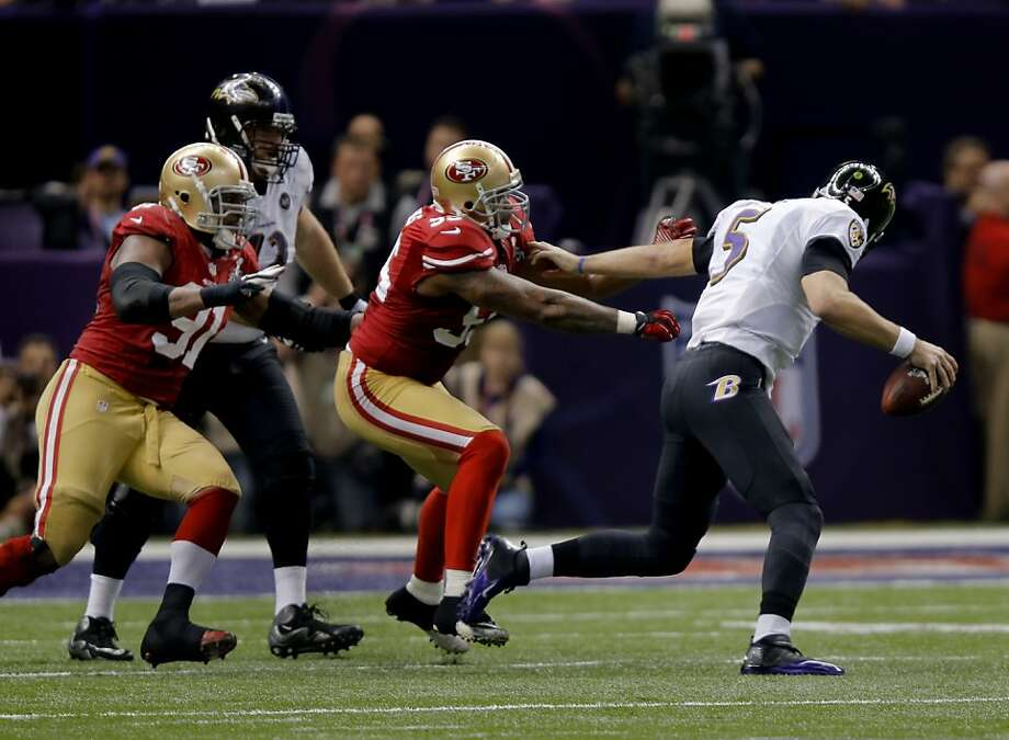Baltimore quarterback Joe Flacco broke away from two 49er defenders in the fourth quarter but couldn't complete the pass. The Baltimore Ravens defeated the San Francisco 49ers in Super Bowl XLVVII 34-31 Sunday February 3, 2013. Photo: Brant Ward, The Chronicle