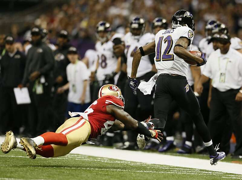 Baltimore Ravens wide receiver Jacoby Jones (12) catches a long pass through the attempted tackle of