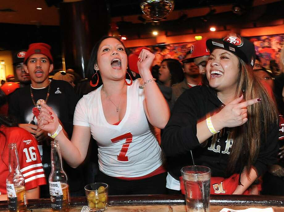 Jennifer Estaris (left) and Cat Duong watch the San Francisco 49ers against the Baltimore Ravens during the Super Bowl at Jillians in San Francisco on February 3, 2013. Photo: Susana Bates, Special To The Chronicle