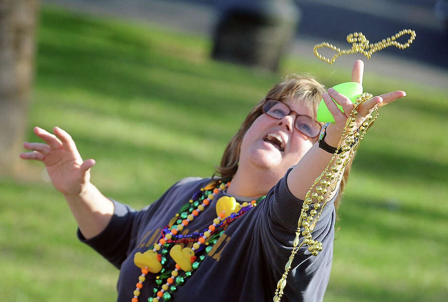 A Mardi Gras fan reaches for a string of beads along Woodworth Boulevard during the festival's final parade on Sunday.  Photo taken Sunday, March 6, 2011. Guiseppe Barranco/The Enterprise Photo: Guiseppe Barranco