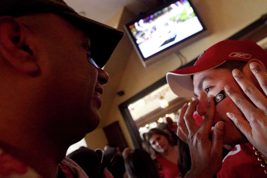 Sathya Sundaram, left, places a 49ers sticker on Manny Epigmenio  before the start of the Super Bowl at Maggie McGarry's on Grant St. in San Francisco. Photo: SF Gate / Douglas Zimmerman