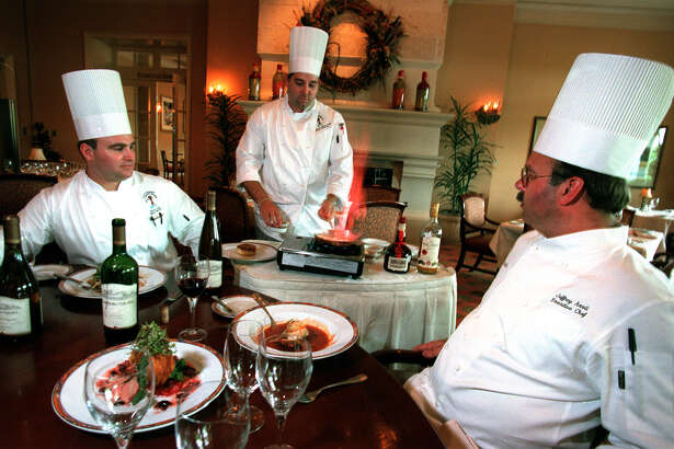 SA LIFE DINNING - ADV- Preparing for the Wine Dinner at the Hyatt Regency Hill Country Resort, Executive Chef Jeffrey Axell, right , and Billy Skiber, left, Sous Chef of Antler Lodge, watch Brain Nichols, Executive Sous Chef make Flamed White Peach and Praline Sauce. photo Bob Owen