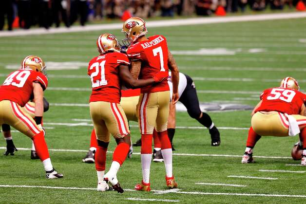 San Francisco 49ers Quarterback Colin Kaepernick (7) talks with running back Frank Gore (21) before a play during the first quarter of Superbowl XLVII between the San Francisco 49ers and the Baltimore Ravens at the Mercedes-Benz Superdome on Sunday February 3, 2013 in New Orleans, La. Photo: Carlos Avila Gonzalez, The Chronicle / ONLINE_YES