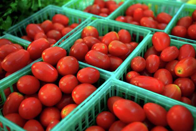 FILE - In this Wednesday, Nov. 7, 2012, file photo, tomatoes are sold at the Union Street Farmer's Market in downtown Gainesville, Fla. Cheaper gas drove down a measure of wholesale prices in November for the second straight month, a sign inflation remains in check. (AP Photo/The Gainesville Sun, Erica Brough)  THE INDEPENDENT FLORIDA ALLIGATOR OUT Photo: Erica Brough, Associated Press / The Gainsville Sun