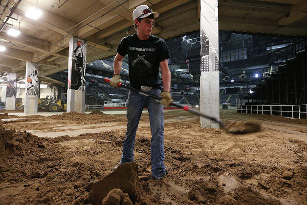 A dozen volunteers began covering the AT&T Center with up to a foot of dirt — depending on how you measure it, about 70 truckloads or 1,600 cubic yards weighing 2,160 tons — to prepare the arena for San Antonio Stock Show & Rodeo events.The rodeo soil was bought near Charlotte in 1988. After the show, it will be removed and stored for next year. Sand and water gets added to it, and it's screened every other year. Having a stockpile saves the rodeo at least $20,000 a year, officials said. Photo: JERRY LARA, San Antonio Express-News / © 2013 San Antonio Express-News