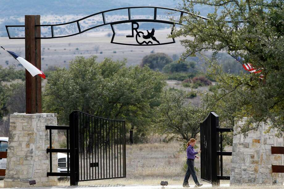An employee opens the gate to let out cars at the entrance Rough Creek Lodge, Sunday, Feb. 3, 2013. Chris Kyle and Chad Littlefield were found murdered at the gun range on the property. (AP Photo/The Fort Worth Star-Telegram, Richard W. Rodriguez) Photo: Richard Rodriguez, Associated Press / Fort Worth Star-Telegram