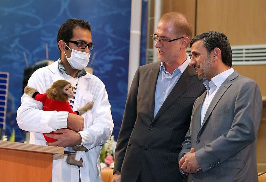 "Volunteer space cadet:Iranian President Mahmoud Ahmadinejad meets a simian astronaut during Iran's National Day of Space Technology in Tehran. Ahmadinejad said he is ready ""to be the first man in space"" sent by the Iranian scientists under an ambitious national program that aims to put a human being into orbit before 2020. Photo: Arman Teimur, AFP/Getty Images"