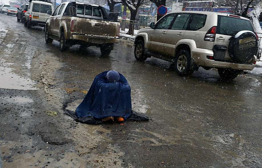 Winter's despair:An Afghan woman begs for alms as she sits in mud and slush in Kabul. Photo: Shah Marai, AFP/Getty Images