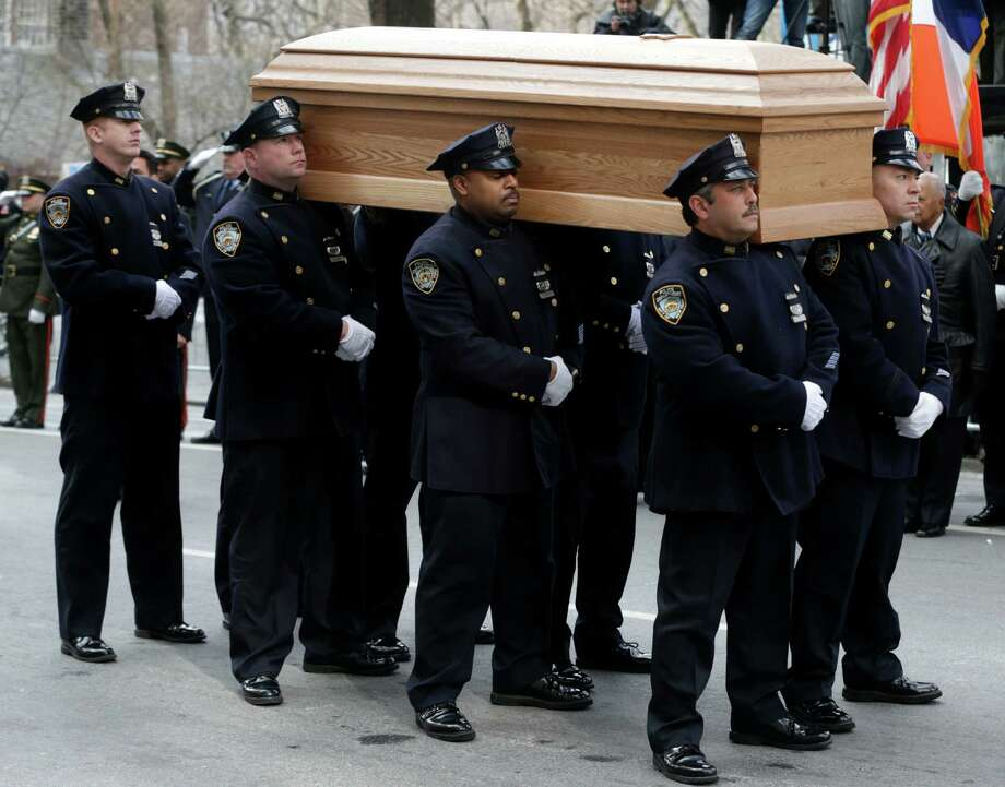 A casket containing the body of former New York City Mayor Ed Koch is loaded into a hearse while city employees, politicians, media and others look on after his funeral in New York, Monday, Feb. 4, 2013. Koch was remembered as the quintessential New Yorker during a funeral that frequently elicited laughter, recalling his famous one-liners and amusing antics in the public eye. Koch died Friday of congestive heart failure at age 88. Photo: Seth Wenig, AP / AP