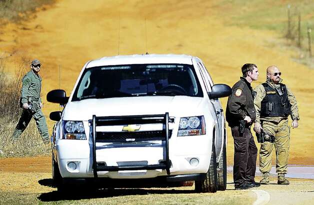 Authorities work a check point, Wednesday, Jan. 31, 2013, in Midland City, Ala., below the home where Tuesday's school bus shooting suspect is barricaded in a bunker with a five-year-old boy as hostage. Speaking into a 4-inch-wide ventilation pipe, hostage negotiators tried Thursday to talk a man into releasing a kindergartener and ending a standoff in an underground bunker that stretched into its third day. Photo: JAY HARE / Dothan Eagle