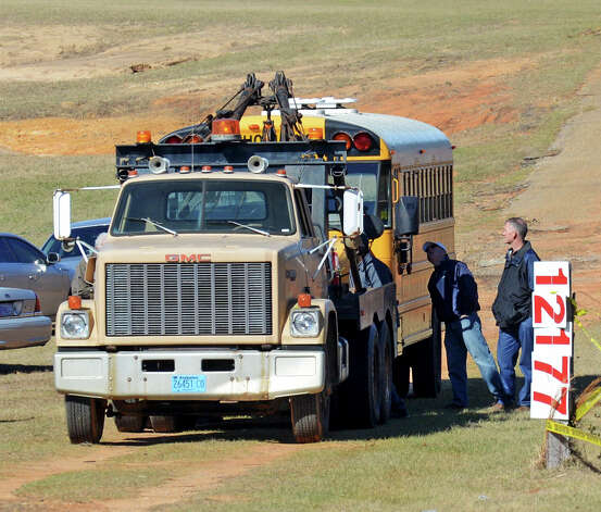 Law enforcement officials remove the bus Friday, Feb. 1, 2013, that Charles Poland was driving when he was fatally shot in Midland City, Ala. Suspect Jimmy Lee Dykes has been holed up in a bunker on his property with the 5-year-old child he took from the bus since the late afternoon shooting on Tuesday, Jan. 29. Photo: Al.com, Julie Bennett