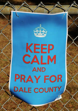 A sign encouraging prayer for a 5-year-old boy being held hostage, hangs on a fence surrounding Midland City Elementary school Wednesday, Feb. 3, 2013, in Midland City, Ala. Authorities say Jim Lee Dykes, 65 — a decorated Vietnam-era veteran known as Jimmy to neighbors — gunned down a school bus driver and then abducted a 5-year-old boy from the bus, taking him to an underground bunker on his rural property. The driver, 66-year-old Charles Albert Poland Jr., who was shot trying to protect children on his bus, was buried Sunday. Photo: AL.com, Joe Songer