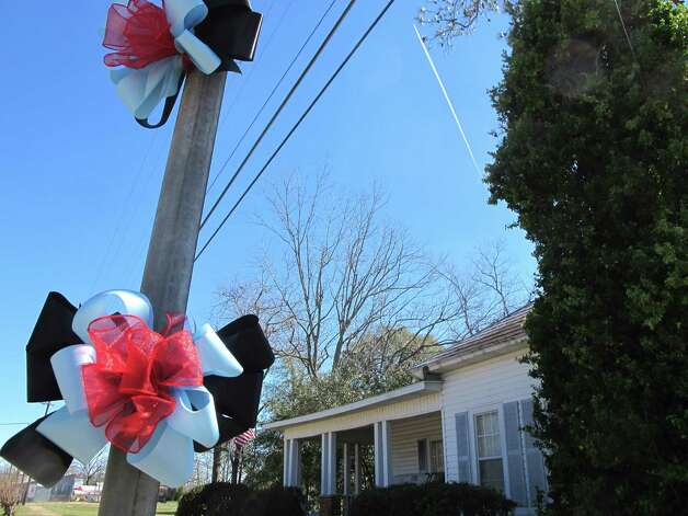 Ribbons adorn a utility pole across from an elementary school in  Midland City, Ala., on Sunday, Feb. 3, 2013. The school is attended by a 5-year-old boy police say is being held hostage by a man who gunned down a school bus driver on Jan. 29, took the child and is holding him in a underground bunker. Photo: Bruce Smith