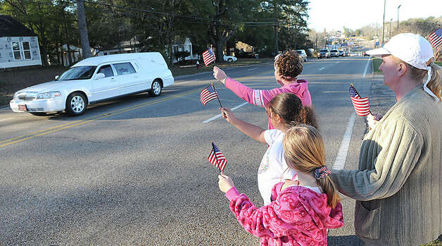 "Residents raise flags along the processional route in Ozark for Dale County Schools bus driver Charles ""Chuck"" Poland Jr., who died Tuesday, in Ozark, Ala., Sunday, Feb. 3, 2013. Authorities say Jim Lee Dykes, 65 — a decorated veteran of the Vietnam War known as Jimmy to neighbors — gunned down Poland, a school bus driver, and then abducted a 5-year-old boy from the bus, taking him to an underground bunker on his rural property. Photo: Dothan Eagle, Danny Tindell"