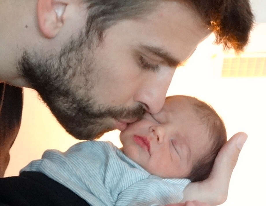 This undated image released courtesy of singer and UNICEF Goodwill Ambassador Shakira shows FC Barcelona star Gerard Pique kissing the cheek of his son Milan, born Jan. 22 in Barcelona. The couple are inviting friends and fans to join their online baby shower to help provide life-saving items to children and communities in some of the poorest corners of the globe. After purchasing an Inspired Gift, they will then receive a personal thank you message from the couple. (AP Photo/courtesy of Shakira)