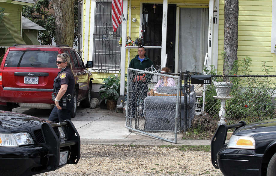 San Antonio police officer Jessica Phelt (left) walks past a Jeep Patriot that was pushed into the front of the home of Beatrice Navarro,70, at 419 North Monumental about 11:00 a.m. Monday February 4, 2013. Phelt said a man between the ages of 17 and 20-years-old driving a white sedan crashed into a parked car on Monumental pushing it about 20 feet. The driver then hit the Jeep, pushing it into the house and fled the scene. The driver then hit some cars in a parking lot and his abandoned vehicle was later found at the Little Red Barn steakhouse on South Hackberry street. Photo: JOHN DAVENPORT, San Antonio Express-News / © San Antonio Express-News